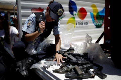 Venezuelan police crushes guns on the streets